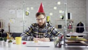 De droevige gebaarde zakenman, beambte viert een eenzame verjaardag in het bureau, blaast hij een kaars op klein stock videobeelden