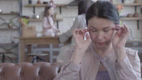 De droevige hogere vrouw zit op de bank, die en veegt haar scheuren van het gezicht af schreeuwen Op de achtergrond haar daugher  stock videobeelden