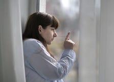 De droevige jonge donkerbruine vrouw kijkt uit het venster, vinger op het glas stock afbeeldingen
