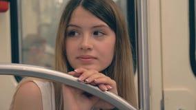 De droevige Jonge Kaukasische Vrouw leunde Haar Hoofd en Hand op het Traliewerk in de Metro stock videobeelden