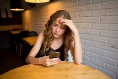 De droevige jonge meisjeszitting in een koffie die vermoeide haar telefoon, ongelukkig meisje die op haar zwarte telefoon letten  royalty-vrije stock foto's
