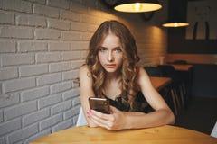 De droevige jonge meisjeszitting in een koffie die vermoeide haar telefoon, ongelukkig meisje die op haar zwarte telefoon letten  stock fotografie