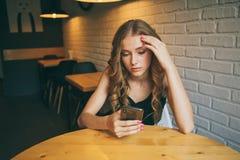De droevige jonge meisjeszitting in een koffie die vermoeide haar telefoon, ongelukkig meisje die op haar zwarte telefoon letten  royalty-vrije stock fotografie
