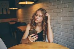 De droevige jonge meisjeszitting in een koffie die vermoeide haar telefoon, ongelukkig meisje die op haar zwarte telefoon letten  stock afbeelding
