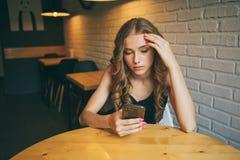 De droevige jonge meisjeszitting in een koffie die vermoeide haar telefoon, ongelukkig meisje die op haar zwarte telefoon letten  stock afbeeldingen