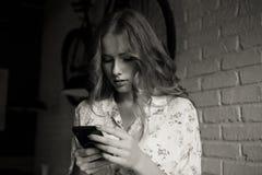 De droevige jonge meisjeszitting in een koffie die vermoeide haar telefoon, ongelukkig meisje die op haar zwarte telefoon letten  royalty-vrije stock afbeeldingen