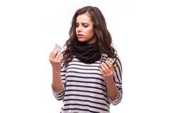 De droevige jonge vrouw die griep hebben neemt pillen Royalty-vrije Stock Afbeeldingen