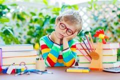 De droevige jongen van het schooljonge geitje met glazen en studentenmateriaal Stock Foto