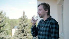 De droevige kerel die aan kater in ochtend lijden en drinkt water stock video