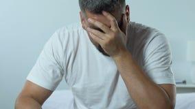 De droevige knappe mensenzitting op de pillen van de bedholding verschroeit, het gezondheidsprobleem van mensen stock footage