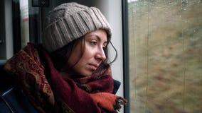 De droevige meisjestoerist kijkt uit het treinvenster stock video