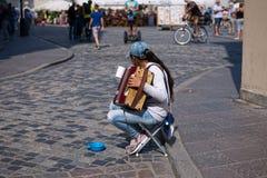 De droevige musicus die van de meisjesstraat kleine harmonika spelen royalty-vrije stock foto