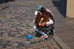 De droevige musicus die van de meisjesstraat kleine harmonika spelen royalty-vrije stock afbeelding