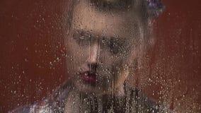 De droevige vrouw met rode lippenstift kijkt nat door het venster van de regen stock footage