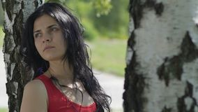 De droevige vrouw na gebroken verhoudingen, alleen in park onder boom kijkt weg langzaam stock video