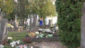 De droevige vrouw zit op bank dichtbij graf van echtgenootvader in begraafplaats Gezoem uit 4K stock videobeelden