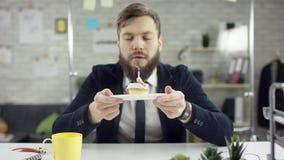 De droevige werkende gebaarde zakenman, beambte viert een eenzame verjaardag in het bureau, blaast hij een kaars stock videobeelden