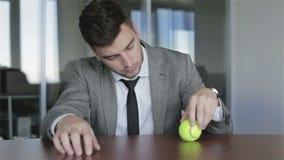 De droevige zakenman mediteert het kijken op de spinnende bal stock video