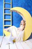 De droevige zitting van het blondemeisje op een gele maan Royalty-vrije Stock Foto