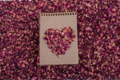 De droge bloemblaadjes vormen een hartvorm op een spiraalvormig notitieboekje Stock Afbeeldingen