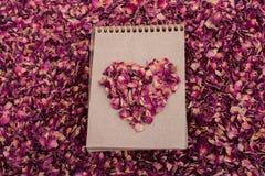 De droge bloemblaadjes vormen een hartvorm op een spiraalvormig notitieboekje Royalty-vrije Stock Afbeelding