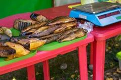 De droge, gerookte vis ligt op de dorpsmarkt op de teller, naast de schalen royalty-vrije stock fotografie
