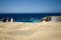 De droge oceaankustklippen en de rotsen, familie genieten van de wilde golven die water bespatten Royalty-vrije Stock Afbeeldingen