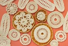 De droge sinaasappelen en de witte uitstekende elementen van het Iers haken Doilies, cirkelonderleggers voor glazen, het creatiev Stock Foto