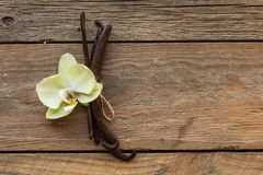 De droge vanillepeulen en bloemen van de orchideevanille op houten achtergrond Vanillesuiker stock afbeeldingen