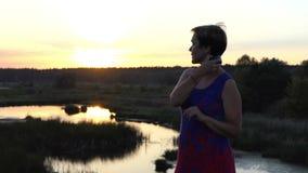 De dromende vrouw kamt haar haar op een meerbank stock video