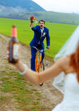 De dronken bruidegom op een fiets die een huwelijksboeket houden loopt na een bruid met een bierfles stock foto's