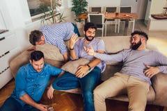 De dronken kerels slapen nadat de nachtgebeurtenissen over de vloer en de bank in verschillend in woonkamer stellen stock foto's