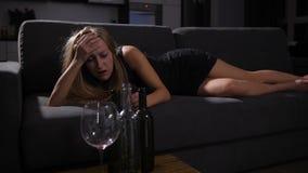 De dronken ontwaken van het partijmeisje op bank met kater stock videobeelden
