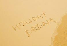 De droom van de vakantie die in het zandige strand wordt geschreven Stock Foto's