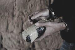 De drugdealer onder arrestatie beperkte met handcuffs samen met heroïne, Wet en politieconcept Wereld Antidrugdag stock foto's
