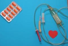 De drugs op een blauwe achtergrond voor de behandeling van hartkwaal, druppelbuisjenaald en tabletten van oranje kleur, het conce Stock Foto's