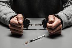 De drugverslaafde werd gearresteerd voor druggebruik bij de lijst het lijden aan verslaving op een donkere zwarte achtergrond royalty-vrije stock afbeeldingen