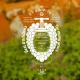 De druiven bundelen met omhoog vat voor tekst in het centrum en de uitstekende pers Wijnetiket op wijngaarden en huis vage achter Stock Afbeeldingen