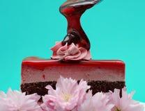 De druppel van de aardbeiglans op stuk van aardbei en chocolade bracht aanin lagen cake op turkooise achtergrond royalty-vrije stock foto's