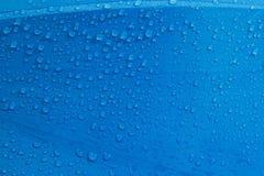 De druppeltjes van het regenwater op blauwe vezel Stock Foto