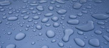De druppeltjes van het water op blauwe auto Stock Foto