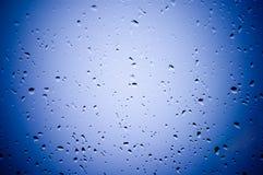 De druppeltjes van het water op blauwe gla Stock Fotografie