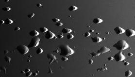 De druppeltjes van het water op een zwarte achtergrond Stock Foto's