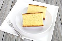 De duas partes do bolo de esponja na placa branca na tabela de madeira Fotografia de Stock Royalty Free