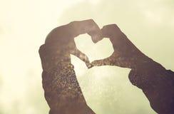 De dubbele blootstelling van abstract dubbel blootstellingsbeeld van handensilhouet in de vorm van hart en schittert textuur Retr Stock Foto's
