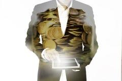 De dubbele blootstelling van de bedrijfsman werkt aan de tablet en de gouden muntstukken in kruik, het concept van de investering Stock Afbeelding