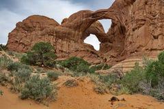De dubbele die bogen door rood zand en groene woestijn worden geaccentueerd schrobben in Boog Stock Fotografie