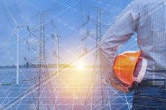 De dubbele tribune die van de blootstellingsingenieur gele veiligheidshelm in zonnekrachtcentrale met windturbines en hoogspannin stock foto's