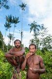 De dubbla ståendeKorowai männen på den naturliga gröna skogbakgrunden Arkivbild