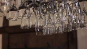 De duidelijke wijnglazen hingen over de bar, afwezen bocal stock videobeelden